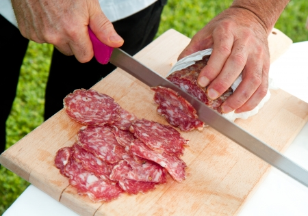 Hand closeup cuts salami with slice pieces at table  photo