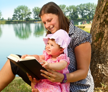 beautiful little girl reading book with her mother photo