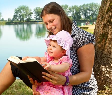 mujer hijos: hermosa niña libro de lectura con su madre