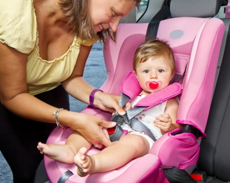 vehicle seat: Woman fastening her son on a baby seat in a car
