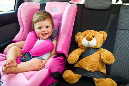 vehicle seat: baby girl with his teddy bear smile in car