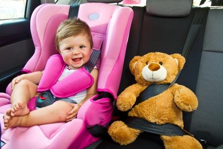 cinturon seguridad: ni�a con su osito de peluche sonrisa en el coche Foto de archivo