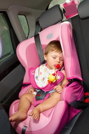 asiento coche: Bebé bebé duerme tranquilamente asegurado con el cinturón de seguridad mientras que en el coche.