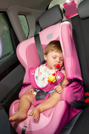 Infant baby sleeps peacefully secured with seat belts while in the car.  photo