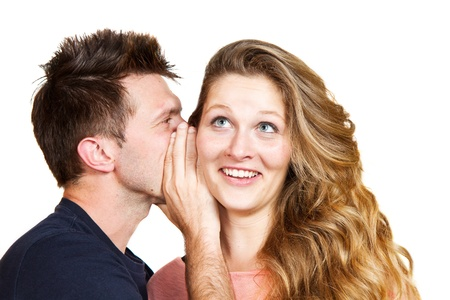 Portrait of a handsome young man whispering a secret to a cute woman against white  photo