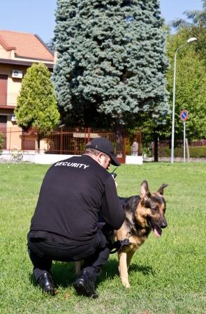 perro policia: parte trasera de un guardia de seguridad con un perro