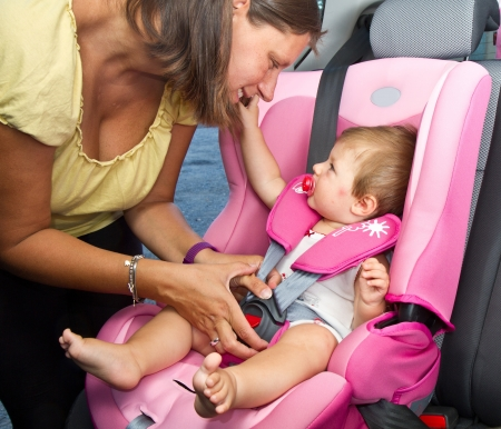 Woman fastening her son on a baby seat in a car