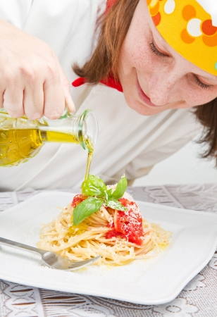 smiling chef garnish an Italian pasta dish  photo