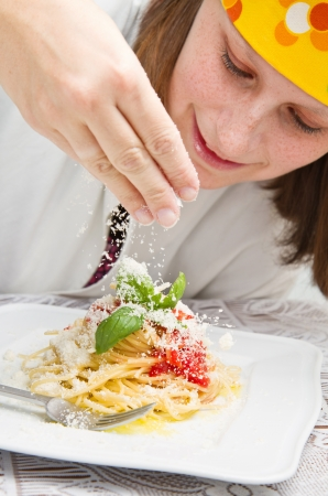 smiling chef garnish an Italian pasta dish with cheese photo