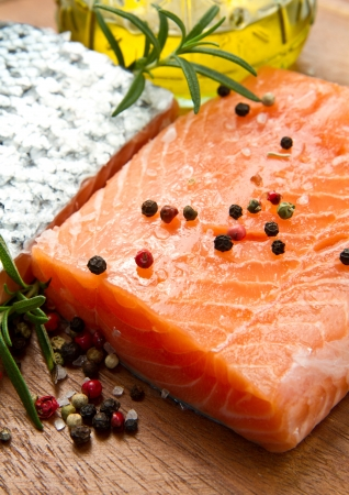 Fresh salmon fillet on wooden board with pepper and rosemary photo