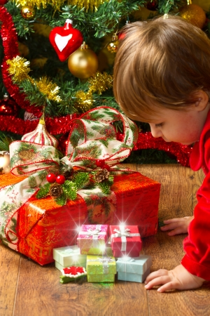 baby open present: baby play with present box at Christmas tree Stock Photo
