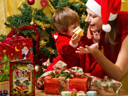 Young mother with  baby  at Christmas tree Stock Photo - 16010372