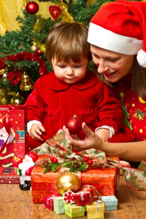 Young mother with  baby  at Christmas tree Stock Photo - 16010377