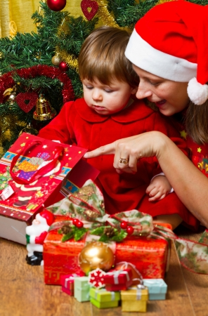 santa s helper: Young mother with  baby  at Christmas tree