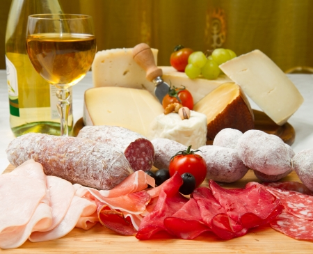 composition of cold cuts on wooden board with different type of cheese