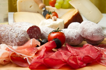 wood cut: composition of cold cuts  on wooden board with different type of cheese  Stock Photo