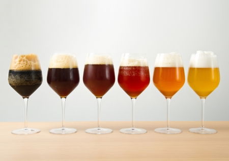 Six glasses with different beers on wooden table photo