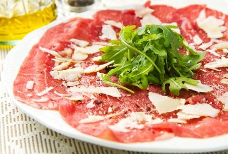 carpaccio: white dish with carpaccio of beef on arugula
