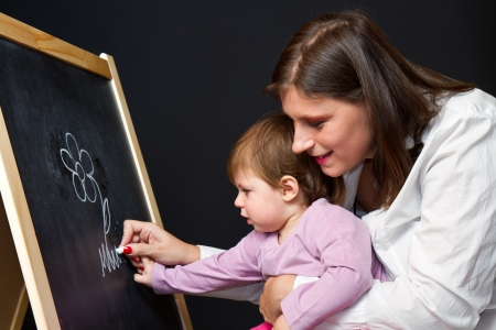 Mother and little daughter writing on a blackboard photo