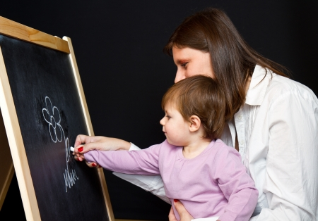 Mother and little daughter writing on a blackboard Stock Photo - 16334326