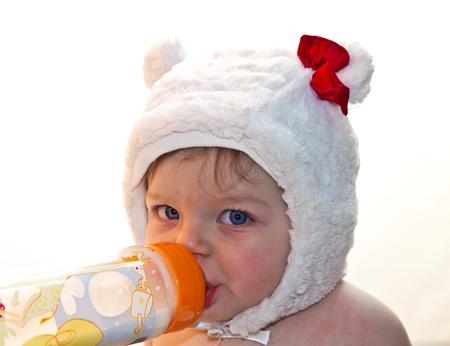sucking milk: Pretty baby girl drinking milk from bottle  Stock Photo