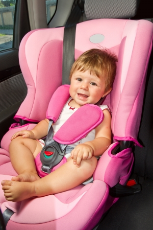 Cute baby enjoying a road trip in a baby car seat photo