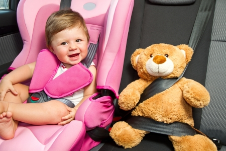 safety: Cute baby enjoying a road trip in a baby car seat