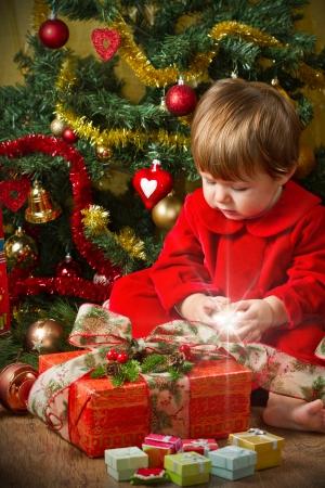 baby near christmas tree: baby play with present box at Christmas tree Stock Photo