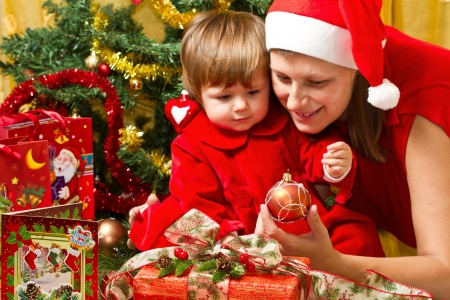 baby open present: Young motherwith  baby  at Christmas tree