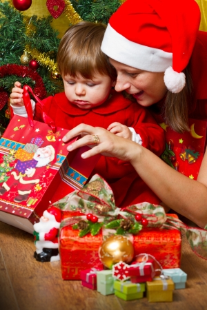 baby open present: Young mother with  baby  at Christmas tree