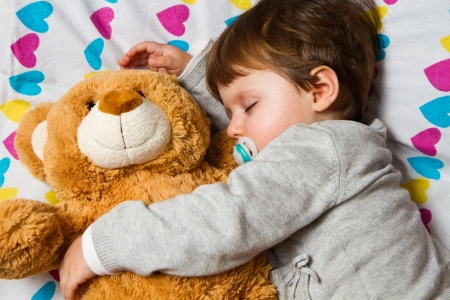 Sweet child sleeping with teddy bear  photo