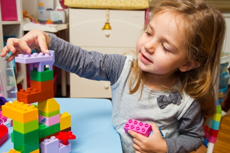 childcare: Little girl is playing with building bricks