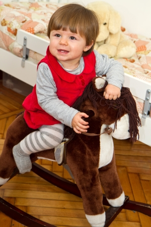 Happy little child and a rocking horse   photo