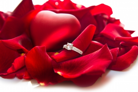 Golden diamond ring and red rose petals  photo