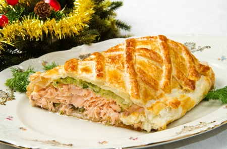 salmon dinner: Traditional salmon in puff pastry with spinach and zucchini in christmas table Stock Photo