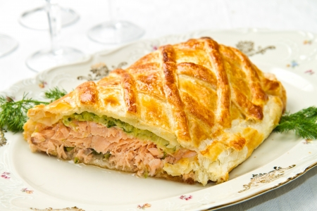 Traditional salmon in puff pastry with spinach and zucchini photo