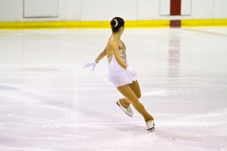woman figure skater performing  on ice photo