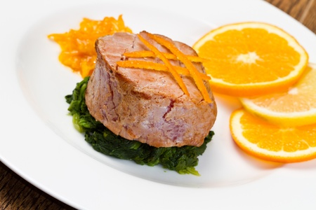 fried tuna fillet with fresh orange ,orange sauce and spinach photo