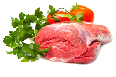 Piece of raw beef with parsley and tomatoes - isolated on white  photo