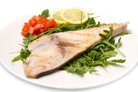 황새치: 하얀 접시에 레몬, 샐러드, 토마토와 구운 황새치 스톡 사진