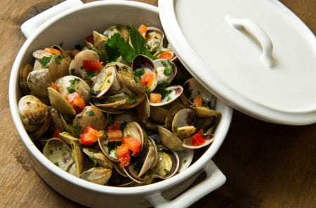 a delicious clams soup with tomatoes on white bowl photo