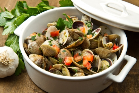 a delicious clams soup with tomatoes on wooden table photo