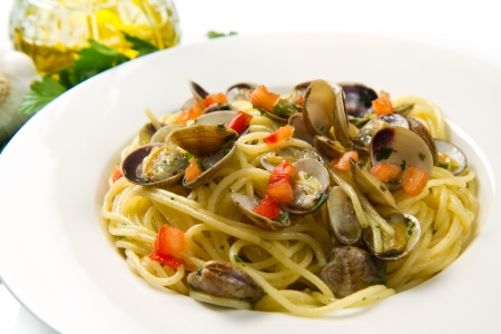 white dish of spaghetti,clams , tomatoes, oil and parsley photo