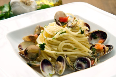 dish of spaghetti with clams on wooden table photo