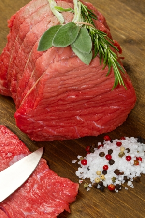 Raw beef on wooden table with rosemary ,sage and salt Stock Photo - 17510954