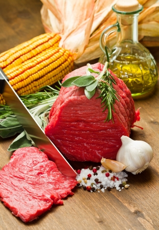 Raw beef on wooden table with rosemary ,sage , salt, cob and garlic Stock Photo - 17510950