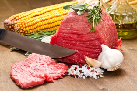 Raw beef on wooden table with rosemary ,sage , salt, cob and garlic Stock Photo - 17510951
