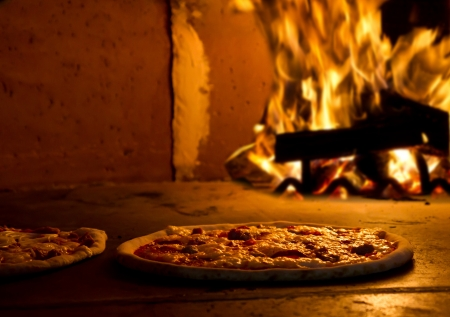 Wood work: an italian Pizza baking in the oven