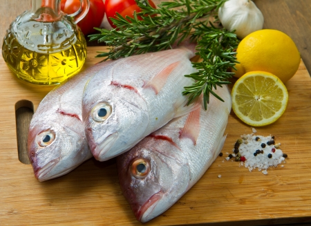 a group of sea bream with lemon and rosemary on wood table Stock Photo - 17842724