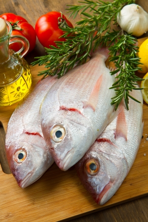 a group of sea bream with lemon and rosemary on wood table Stock Photo - 17842726